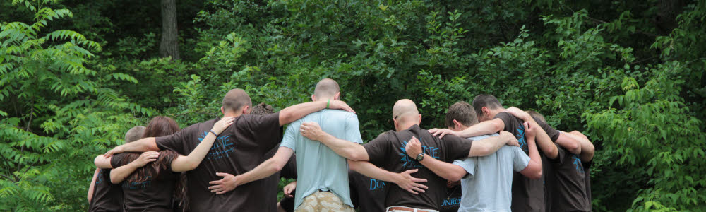 DLITE youth and counselors huddling in a group